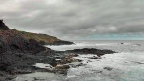 Stormachtig oceaan, wit schuim van de golven die de kustlijn, ertsaders van bevroren vulkanische lava raken Op de achtergrond zij stock videobeelden