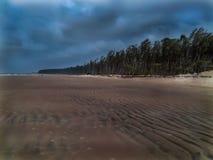 Stormachtig strand bij kust met bewolkte mening Stock Fotografie