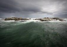 Stormachtig weer op de oceaan met een eiland Stock Foto