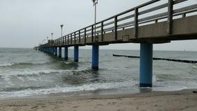 Stormachtig weer op Oostzeestrand golven bij de golfbrekers en de bellen in achtergrond overzeese brug van Graal MÃ ¼ ritz Duitsl stock video