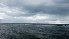 Stormachtige avond bij het ruwe overzees met bewolking van zware wolken en zonnestralen stock video