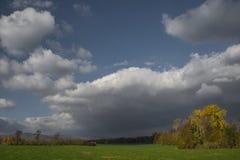 Stormachtige donkere wolken over de bomen en het gebied De dalingsscène Stock Foto