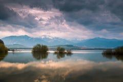 Stormachtige hemel over het meer en mountaines met sneeuw Stock Afbeeldingen