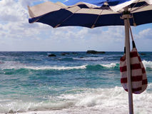 Stormachtige oceaan in een zonnige dag & strandparaplu stock afbeelding