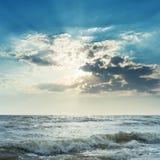Stormachtige overzees en zon in donkere wolken Stock Foto's