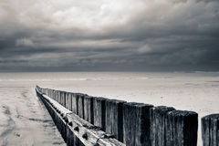 Stormachtige strandomheining in zwart-wit sepia Stock Fotografie