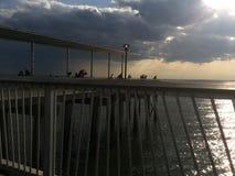Stormachtige wolken met zonsondergang over pijler en oceaan stock afbeelding