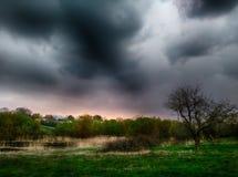 Stormachtige wolken onder groen landschap stock afbeelding