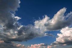 Stormachtige wolken op de blauwe hemel vóór de zonsondergang stock foto