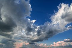 Stormachtige wolken op de blauwe hemel vóór de zonsondergang stock foto's