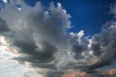 Stormachtige wolken op de blauwe hemel vóór de zonsondergang royalty-vrije stock afbeelding
