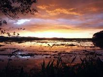 Stormachtige zonsondergang boven meer Stock Foto