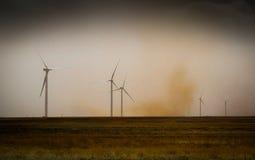 Stormbyn förbigår vindturbiner Arkivfoton