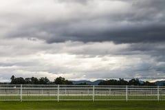 Stormclouds στο σούρουπο πέρα από μια κενή πίστα αγώνων αλόγων Στοκ εικόνες με δικαίωμα ελεύθερης χρήσης