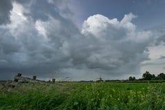 Stormclouds gromadzenie się nad szeroko otwarty holenderską wsią fotografia stock