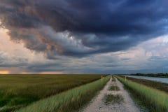 Stormen hägrar över grusvägen royaltyfria foton