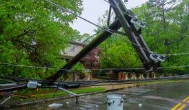 Stormen orsakade sträng skada till fallande lutande för elektriska poler royaltyfria bilder