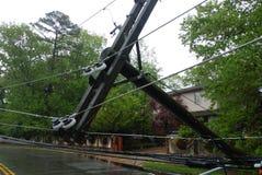 Stormen orsakade sträng skada till fallande lutande för elektriska poler arkivbild