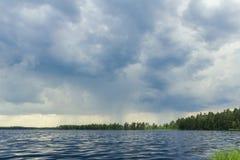Stormhimmel på skogsjön för regn Arkivbilder