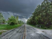 Stormig dag ner en tom väg arkivfoton