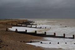 Stormig engelskastrand med vågbrytare Arkivbild