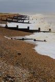 Stormig engelskastrand med vågbrytare Arkivbilder