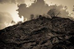 Stormig ensam bergöverkant som ser upp royaltyfri bild