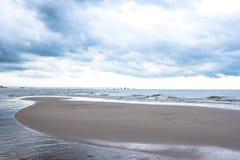 Stormig himmel över det mörka sand och havet Royaltyfria Bilder