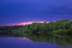 Stormig himmel över floden på natten i sommar arkivbild