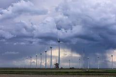 Stormig himmel med duschen över den gamla väderkvarnen och turbiner arkivfoton