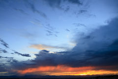 Stormig solnedgång över bergskedja Arkivbild