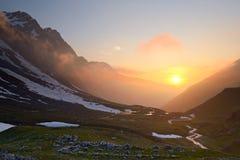 Stormig solnedgång i fjällängarna Arkivbild