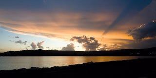 Stormig solnedgångseascape till och med intelligens för apelsin- och svartstormmoln Arkivbild