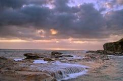Stormig soluppgångstrand Royaltyfri Bild