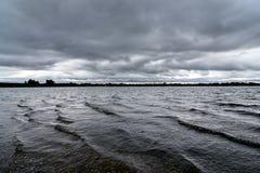 Stormiga himlar som bryggar över en sjö i Staffordshire, England Royaltyfri Bild