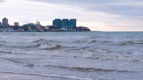Stormiga l?nga v?gor p? strand- och havsport med kuststaden p? bakgrund arkivfilmer
