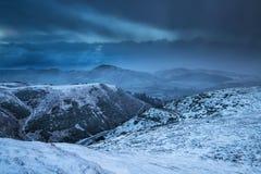 Stormiga moln över berg som täckas i snö royaltyfri bild