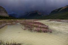Stormiga regnclowds över högt vatten Arkivbild