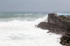 Stormigt hav under tyfonen, vågor som kraschar på barriärväggen Royaltyfri Foto