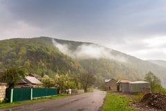 Stormigt regnigt väder för vår Väg och by i grönt berg Fotografering för Bildbyråer