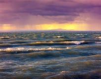 Stormigt regnigt väder på solnedgången på havet Arkivbild