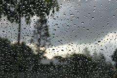 Stormigt tropiskt landskap till och med fönster med regn tappar bakgrund royaltyfria bilder