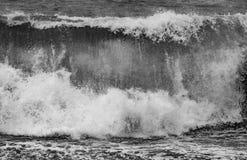 Stormigt väder på den svarta stranden med höga vågor arkivfoto