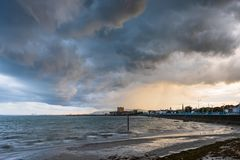 Storming the Castle from above. Large storm clouds gather over Belfast Lough and Carrickfergus Castle, County Antrim, Northern Ireland royalty free stock photo