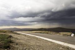Stormmörker fördunklar över berg Arkivbilder