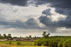 Stormmoln är över lantliga hus Royaltyfri Foto