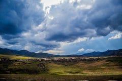 Stormmoln över gräs- kullar royaltyfria bilder