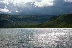 Stormmoln över sjön Seydyavr som omges av berg Arkivbilder