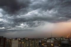 Stormmoln, hällregn Åskväder och blixt över staden Royaltyfri Foto