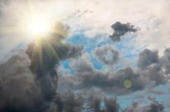 Stormmoln i den blåa himlen och solen, bakgrund Arkivbild